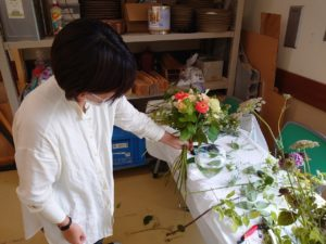 花瓶の大きさに合わせて花束を作る学生