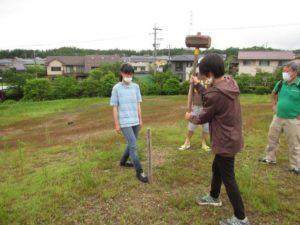 樹木植栽予定地に杭を打つ学生