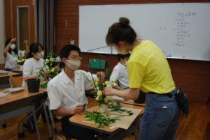 オープンキャンパスに参加した方々にアレンジメントの指導をする学生