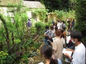 コテージガーデンの前で天野麻里絵さんの説明を聞く学生