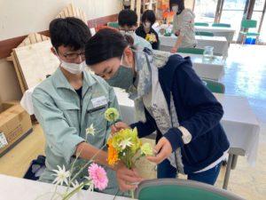 花束制作している高校生をサポートする学生