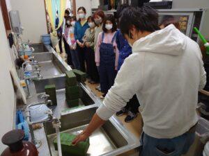 給水スポンジの給水方法の指導を受ける学生ら