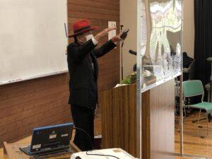 トレードマークの赤い帽子姿での講演