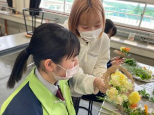 花束制作の指導を高校生にする学生の様子